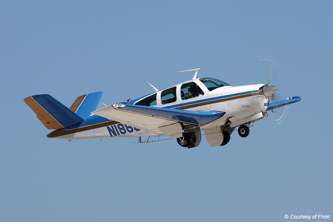 A Vee-tail Beechcraft Bonanza with the gear coming up.
