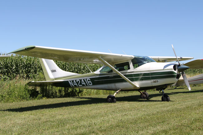 White and green Cessna 182 Skylane parked in field