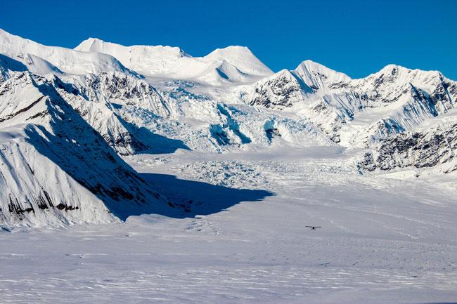 Small plane flies over Alaskan mountains