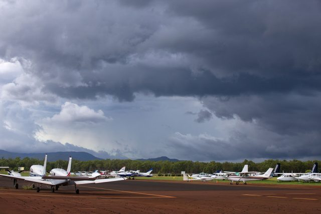 Small planes with storm clouds overhead