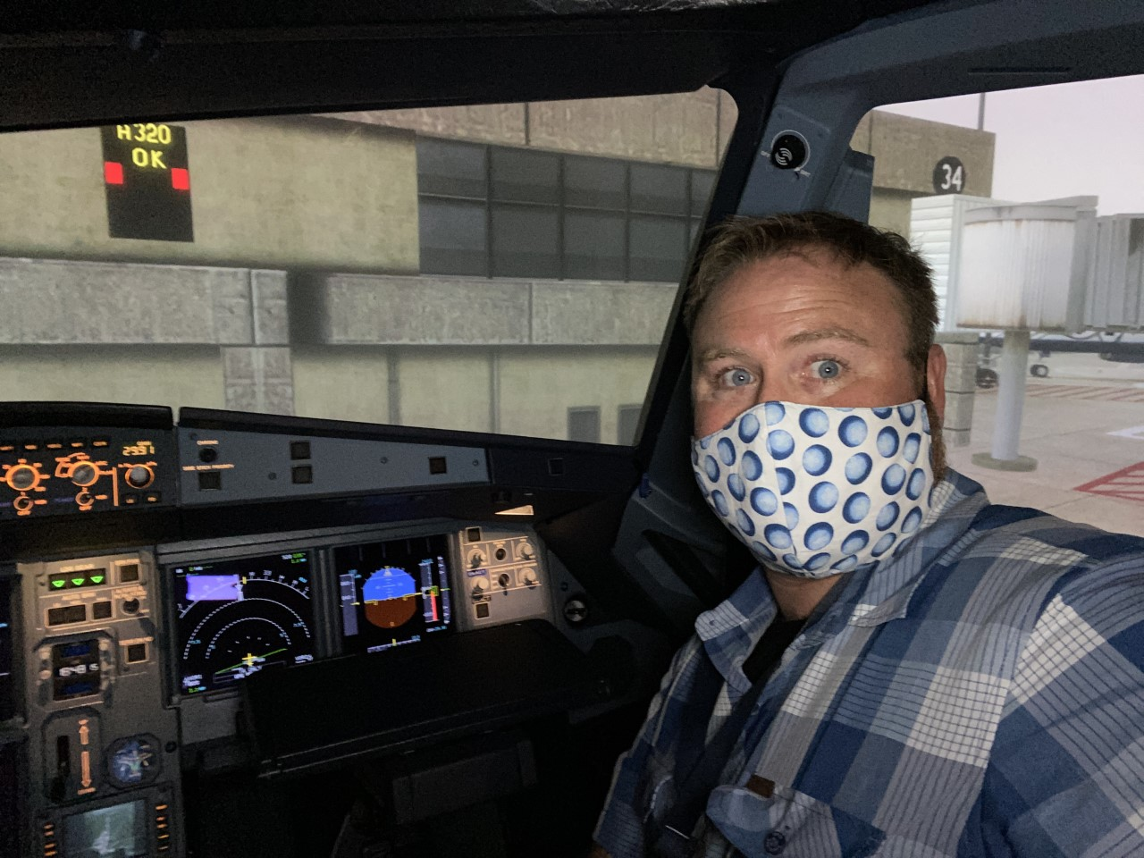 """The author, the pandemic beard """"hidden under the mask,"""" in the Airbus simulator getting ready to knock the rust off. Photo by Jeremy King"""